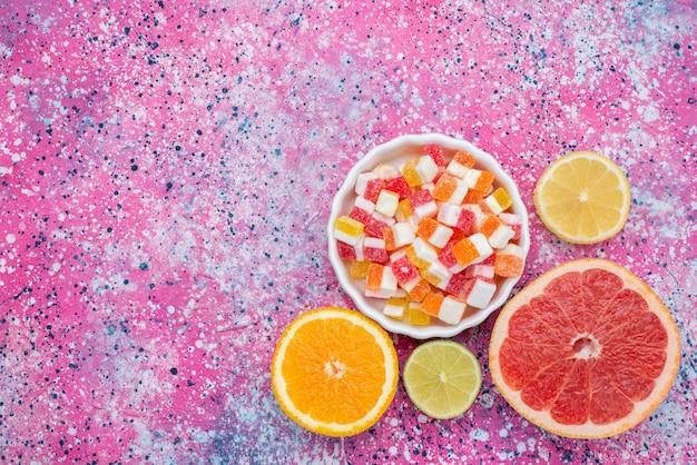 Draufsicht verschiedene marmeladen mit geschnittenen zitrusfrüchten auf dem farbigen hintergrundfarbenbonbon-goody-foto