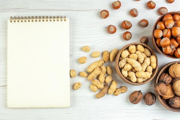 Draufsicht verschiedene nüsse erdnüsse haselnüsse und walnüsse auf weißem tisch
