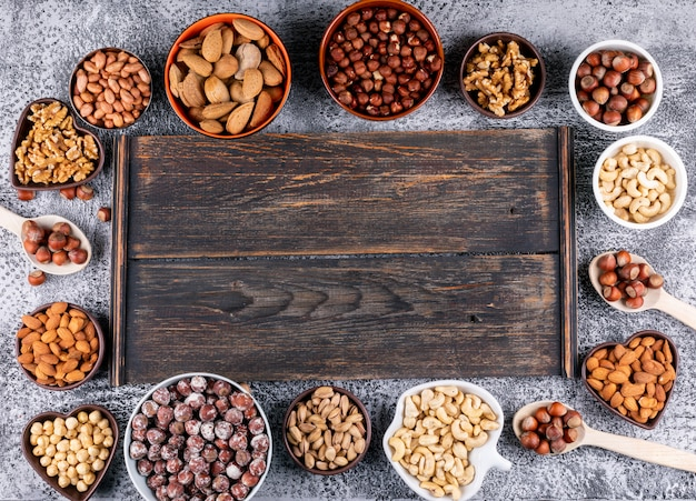 Draufsicht verschiedene nüsse in verschiedenen mini-schalen mit dunklem holzbrett