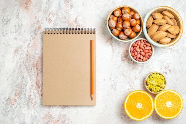 Draufsicht verschiedene nüsse mit in scheiben geschnittener orange auf weißem hintergrund obst zitrus nuss snack