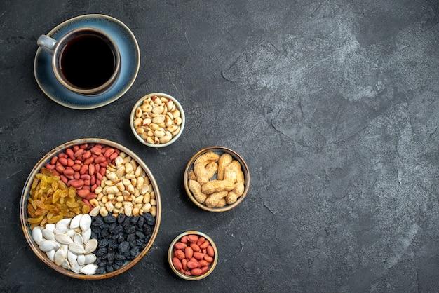 Draufsicht verschiedene nüsse mit rosinen und tasse kaffee auf der dunkelgrauen hintergrundnuss-snack-walnuss-erdnuss