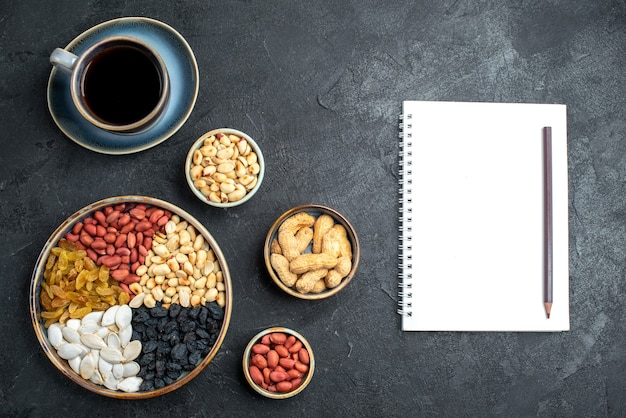 Draufsicht verschiedene nüsse mit rosinen und tasse kaffee auf dunkelgrauer schreibtischnuss-snack-walnuss-erdnuss