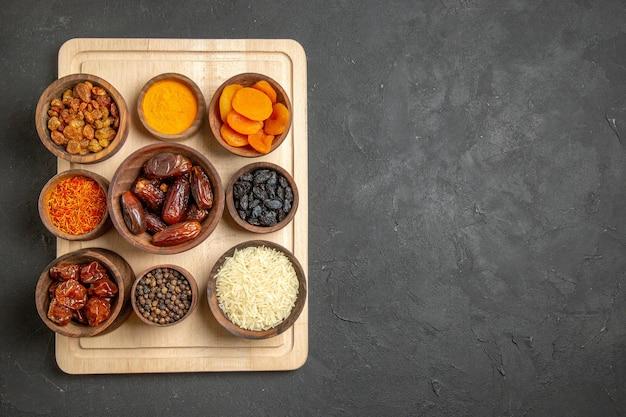 Draufsicht verschiedene rosinen khurma und andere trockenfrüchte auf der grauen oberfläche trockenfrüchtemehl sauer