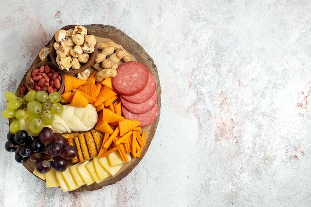 Draufsicht verschiedene snacks nüsse cips trauben käse und würstchen auf dem weißen hintergrund nuss snack mahlzeit lebensmittel früchte