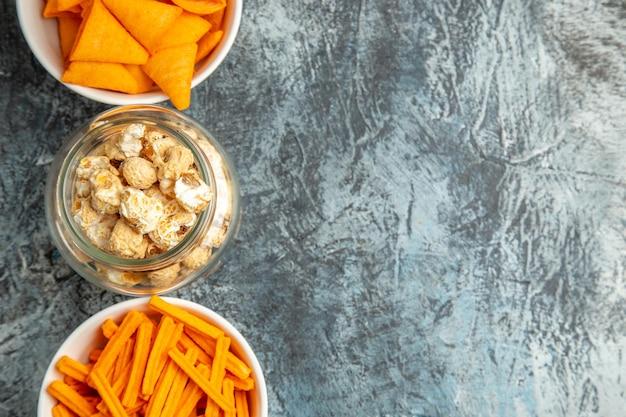 Draufsicht verschiedene snacks popcorn zwieback und cips auf der dunklen oberfläche