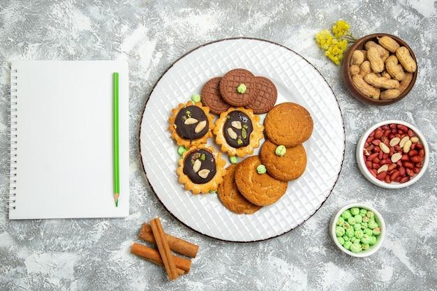 Draufsicht verschiedene süße kekse mit nüssen auf weißer oberfläche