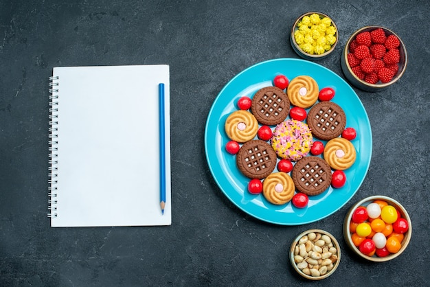 Draufsicht verschiedene zuckerkekse mit bonbons innerhalb platte auf grauer oberfläche süßigkeiten süßer kekskekszucker