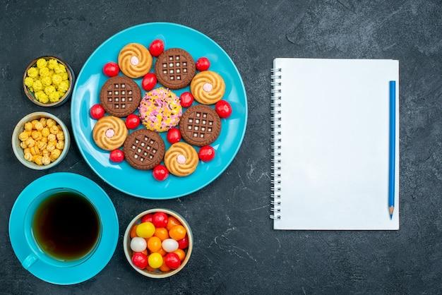 Draufsicht verschiedene zuckerkekse mit süßigkeiten und tasse tee auf grauer oberfläche süßigkeiten zucker süßer tee kekse keks
