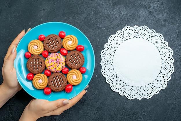Draufsicht verschiedene zuckerplätzchen mit bonbons innerhalb platte auf grauer oberfläche süßigkeiten süßer tee-keks-kekszucker
