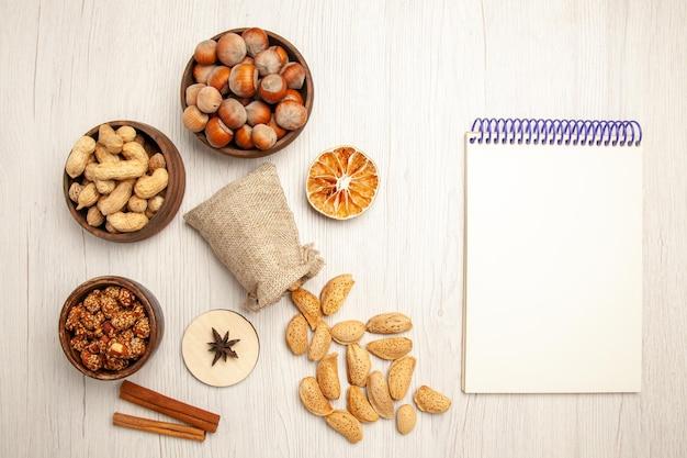 Draufsicht verschiedener nüsse in kleinen töpfen auf weißem schreibtisch nusssnack walnuss haselnuss