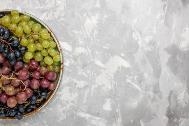 Draufsicht verschiedener trauben saftige milde saure früchte auf weißem schreibtisch