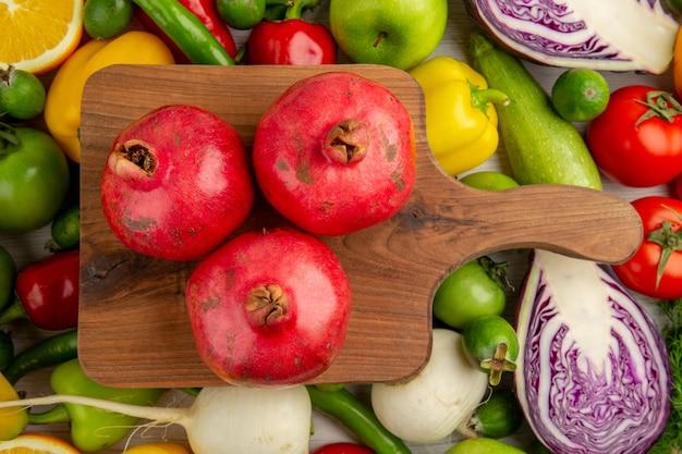 Draufsicht verschiedenes gemüse mit frischen früchten auf weißem hintergrund lebensmitteldiät gesundheit reifen farbsalat