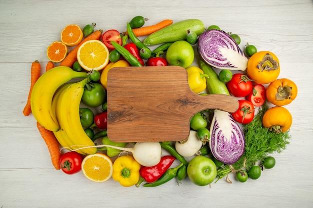 Draufsicht verschiedenes gemüse mit früchten auf weißem hintergrund lebensmitteldiät gesundheit reifen farbsalat