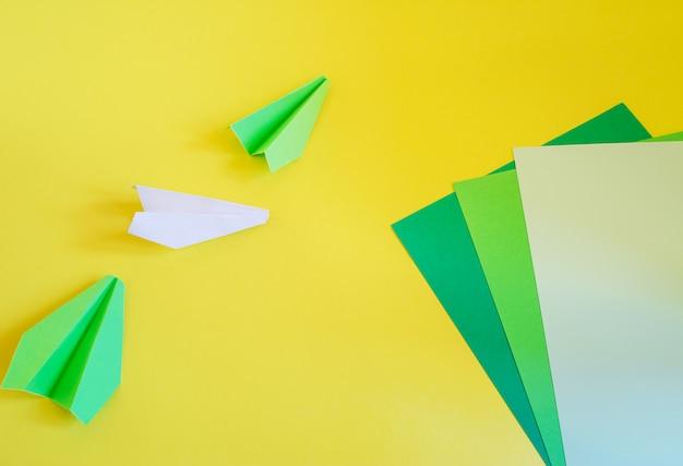 Draufsicht vieler drei papierflugzeuge, die auf gelb legen