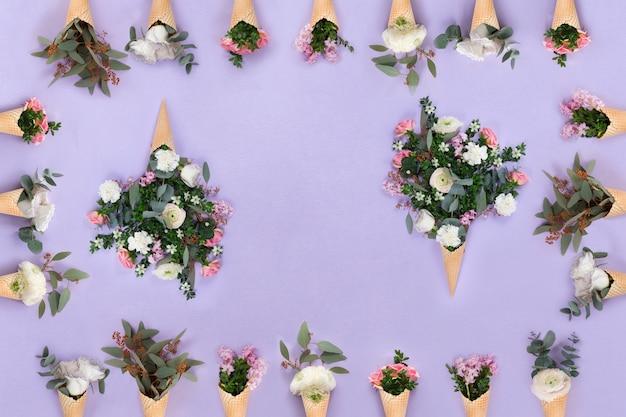 Draufsicht vieler kegel mit blumen auf lila hintergrund, flache lagezusammensetzung mit kopienraum