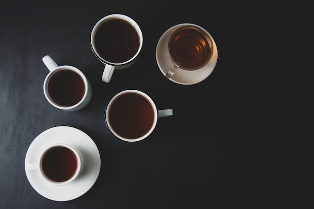Draufsicht vieler schalen, becher mit heißem tee trinken auf dunkelheit, copyspace. teezeit oder teepause. herbstfarbenes, dunkles foto.