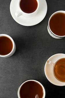 Draufsicht vieler schalen, becher mit heißem tee trinken auf dunkelheit, copyspace. teezeit oder teepause. herbstgetränk. getontes bild mit teetassen.