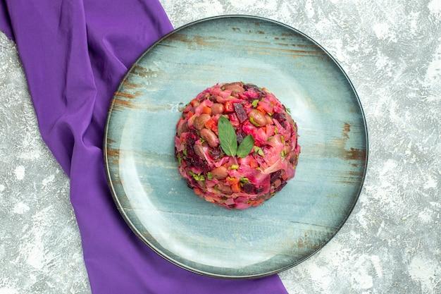 Draufsicht vinaigrette-rüben-kartoffelsalat auf teller lila schal auf leuchttisch