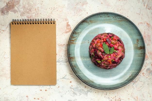 Draufsicht-vinaigrette-salat auf ovalem plattennotizbuch auf hellgrauem tisch