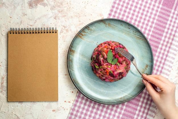 Draufsicht-vinaigrette-salat auf ovalem teller auf weiß-violett karierter tischdecke eine gabel im frauenhandnotizblock auf hellgrauem tisch