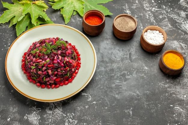 Draufsicht-vinaigrette-salat mit gewürzen auf der dunklen oberfläche