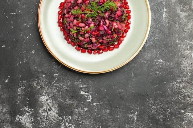 Draufsicht-vinaigrette-salat mit granatäpfeln und bohnen auf dunkler oberfläche