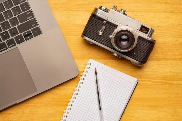 Draufsicht vom bürofotografietisch mit laptop, notizbuch, kamera und stift.