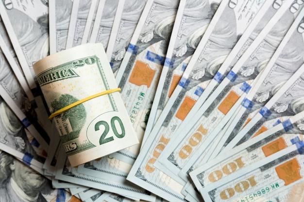 Draufsicht von 20 gerollten dollarscheinen auf hundert dollarbanknoten. unternehmenskonzept