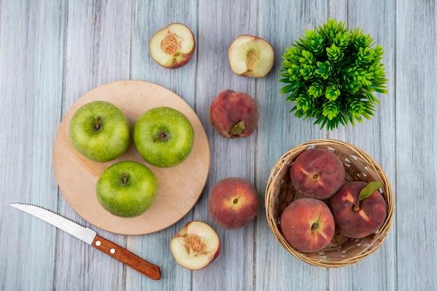 Draufsicht von äpfeln auf schneideküchenbrett mit messerpfirsichen und einem eimer pfirsiche auf grauem holz