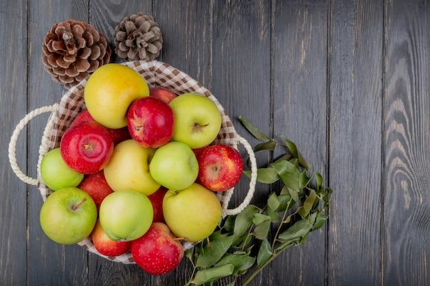 Draufsicht von äpfeln im korb mit tannenzapfen und blättern auf hölzernem hintergrund mit kopienraum