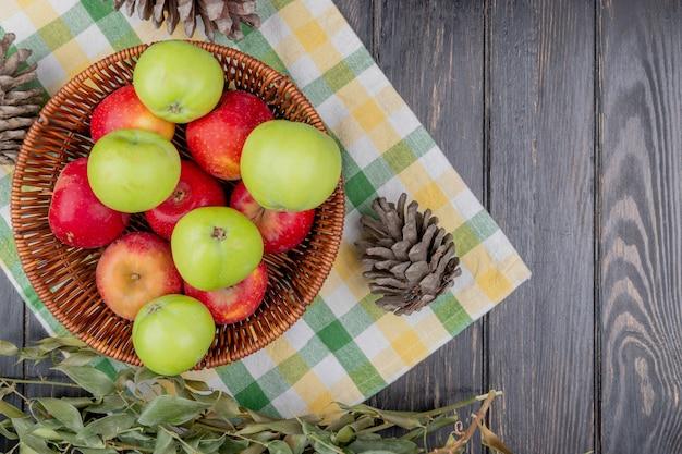 Draufsicht von äpfeln im korb mit tannenzapfen und blättern auf kariertem stoff und hölzernem hintergrund mit kopienraum