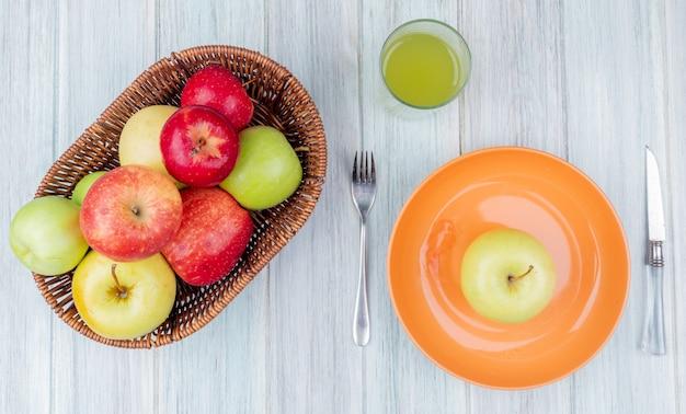 Draufsicht von äpfeln im korb und grünem in platte mit apfelsaftmesser und gabel auf holztisch