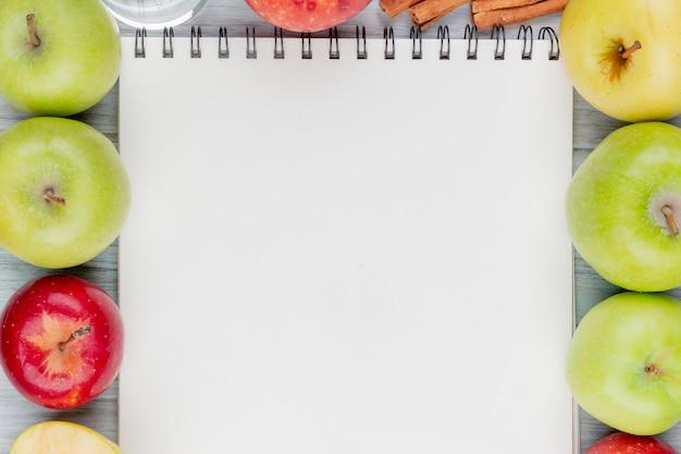 Draufsicht von äpfeln mit zimt und wasser um notizblock auf hölzernem hintergrund mit kopienraum
