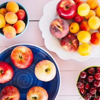 Draufsicht von äpfeln; pflaume; pfirsich und kirschen am schreibtisch aus holz