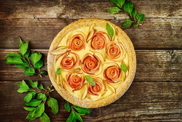 Draufsicht von apfelkuchen mit rosenformapfeldekor und grünen blättern. draufsicht.
