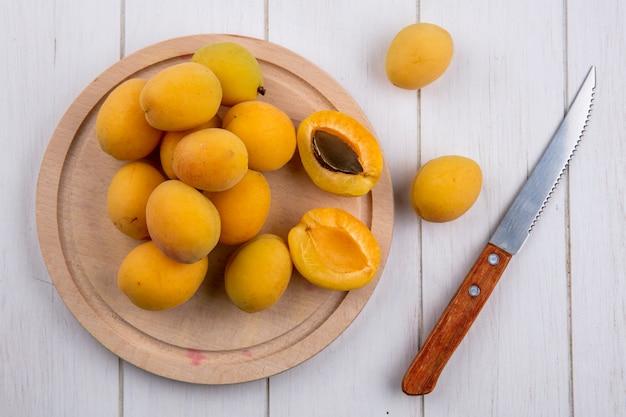Draufsicht von aprikosen auf einem ständer mit einem messer auf einer weißen oberfläche