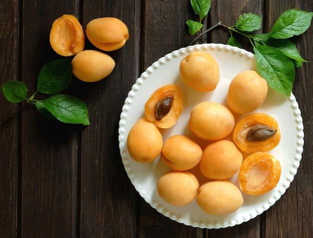 Draufsicht von aprikosen auf einem weißen teller auf weinlesetisch der weinlese