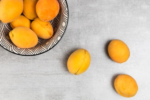 Draufsicht von aprikosen in der schüssel auf hölzernem hintergrund