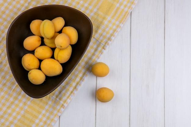 Draufsicht von aprikosen in einer schüssel auf einem karierten gelben handtuch auf einer weißen oberfläche