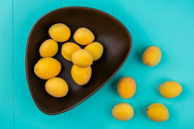 Draufsicht von aprikosen in einer schüssel auf einer blauen oberfläche
