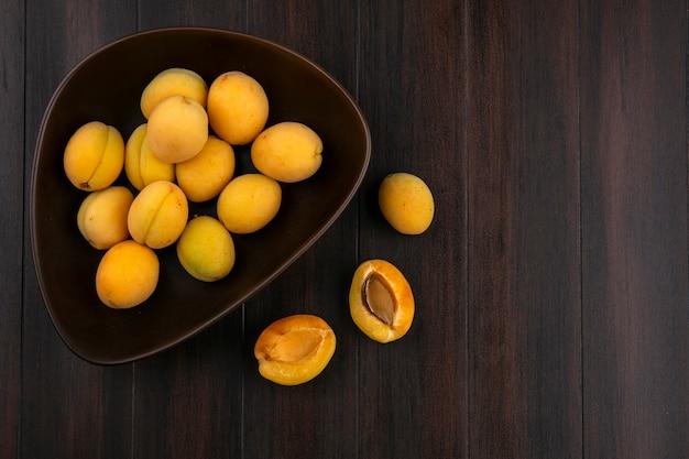 Draufsicht von aprikosen in einer schüssel auf einer holzoberfläche