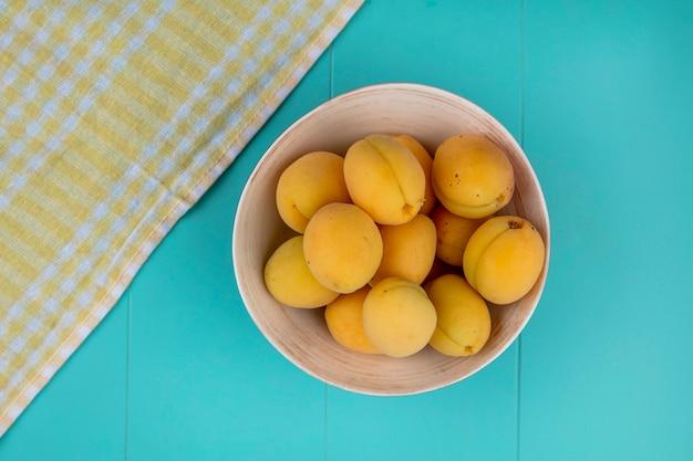 Draufsicht von aprikosen in einer schüssel mit einem gelben karierten handtuch auf einer blauen oberfläche