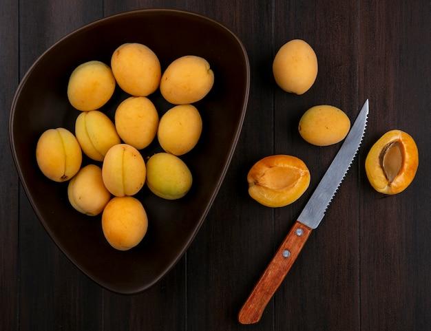 Draufsicht von aprikosen in einer schüssel mit einem messer auf einer holzoberfläche