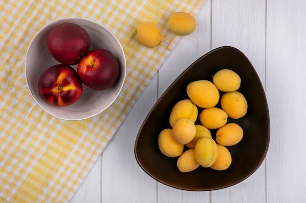 Draufsicht von aprikosen in einer schüssel mit pfirsichen auf einem karierten gelben handtuch auf einer weißen oberfläche