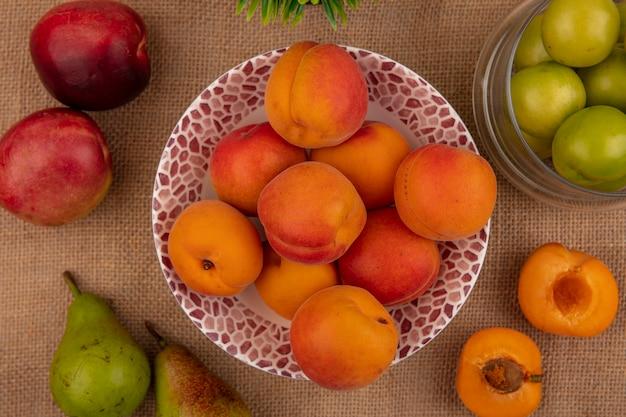 Draufsicht von aprikosen in schüssel und halb geschnittenem pfirsich birnen und schüssel pflaumen auf sackleinenhintergrund