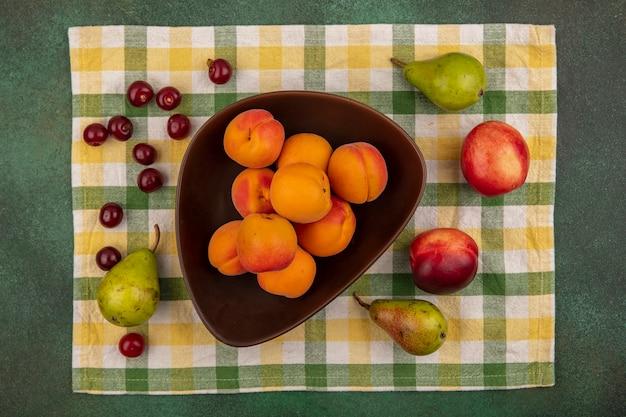 Draufsicht von aprikosen in schüssel und muster der birnenpfirsichkirsche auf kariertem stoff auf grünem hintergrund