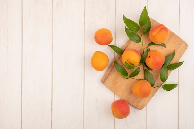 Draufsicht von aprikosen und blättern auf schneidebrett und auf hölzernem hintergrund mit kopienraum