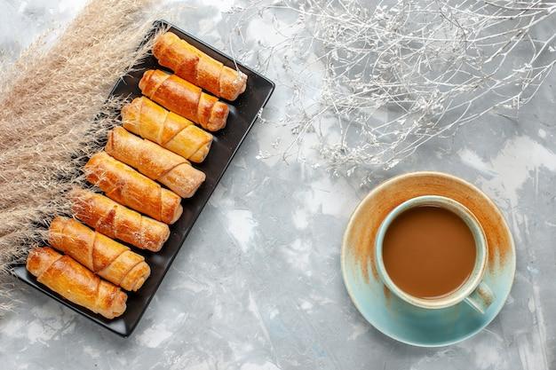 Draufsicht von armreifen mit kaffee auf hellem schreibtisch, süßer gebäckkekskeks