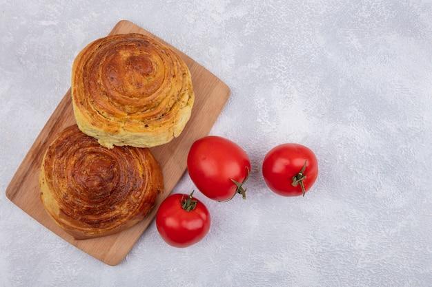 Draufsicht von aserbaidschanischem traditionellem gebäck gogal auf einem hölzernen küchenbrett mit frischen tomaten lokalisiert auf einem weißen hintergrund mit kopienraum