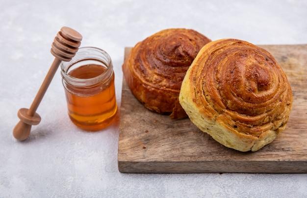 Draufsicht von aserbaidschanischem traditionellem gebäck gogal auf einem hölzernen küchenbrett mit honig auf einem glas auf einem weißen hintergrund
